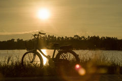 Retro vintage bicycle near the lake at sunset moment. silhouette bicycle at the sunset with grass field.big mountain and sunset. Background.journey concept royalty free stock image