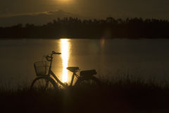 Retro vintage bicycle near the lake at sunset moment. silhouette bicycle at the sunset with grass field.big mountain and sunset. Background.journey concept royalty free stock photos