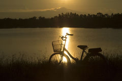 Retro vintage bicycle near the lake at sunset moment. silhouette bicycle at the sunset with grass field.big mountain and sunset. Background.journey concept stock image