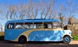 Retro vintage bus profile English countryside. Retro vintage bus in profile in the English countryside beneath a blue sky Stock Image