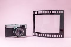 Old fashioned photography camera and photo frame in shape of film tape roll on plain pink background Stock Images