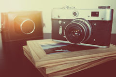 Retro vintage camera and photo frames on wood table Stock Photos