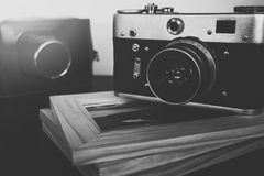 Retro vintage camera and photo frames on wood table Royalty Free Stock Photography