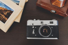 Retro vintage camera and photos in frame on wood background Royalty Free Stock Photography