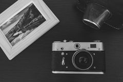 Retro vintage camera and photos in frame on wood background Royalty Free Stock Image