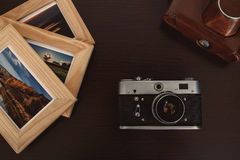 Retro vintage camera and photos in frame on wood background Royalty Free Stock Photos