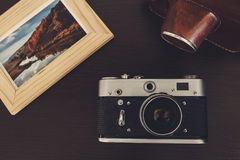 Retro vintage camera and photos in frame on wood background Royalty Free Stock Images