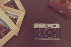 Retro vintage camera and photos in frame on wood background Stock Photo