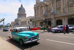Retro vintage car near the Capitol house of Havana. Cuba, Havana - 07 April, 2016: Retro taxi driving on the avenue of Havana, traffic consists mainly of Royalty Free Stock Photography