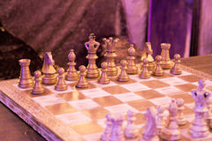 Retro vintage chess in night private club. Blue and violet light Stock Photography
