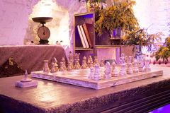 Retro vintage chess in night private club. Blue and violet light Royalty Free Stock Photos