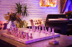 Retro vintage chess in night private club. Blue and violet light Royalty Free Stock Images