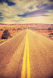 Retro vintage filtered picture of a country highway. Royalty Free Stock Photo