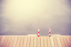 Retro vintage filtered wooden pier and ladder. Royalty Free Stock Photos