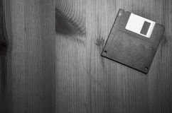 Retro vintage floppy disc close up  on wooden background in black and white. On wooden background Stock Photo