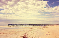 Retro Vintage instant filter wide open beach with beautiful cloud sky. And jetty pier in background royalty free stock photos