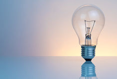 Retro vintage light bulb with on warm light background Royalty Free Stock Photos