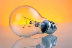 Retro vintage light bulb with on warm light yellow tint background Stock Photos