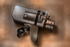 Camera movie vintage on a scratched and textured brown background. An old 50`s camcorder mixes the colors of the past with the memories of entire families. He Royalty Free Stock Photography