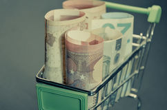 Retro vintage photo effect of Euro banknotes in the shopping cart. Easy access on loan. Stock Photos