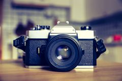 Retro vintage photography camera on a wooden table, blurry background. Retro vintage photography camera on kitchen table, blurry background old fashioned style stock photo
