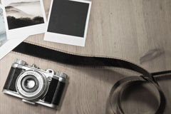 Retro vintage photography concept of three instant photo frames cards on wooden background with old camera and film strip Stock Images