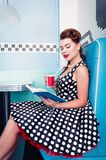 Retro vintage portrait of alluring young girl sitting in cafe and reading book. Pin up style portrait of young girl in dress Stock Photos