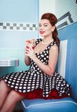 Retro vintage portrait of cheerful beautiful young girl sitting in cafe and drinking beverage. Pin up style portrait of young gi Royalty Free Stock Image