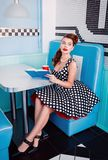 Retro vintage portrait of pretty young girl sitting in cafe with book and beverage. Pin up style portrait of young girl in dress Royalty Free Stock Images