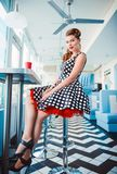 Retro vintage portrait of smiling cute young girl sitting in cafe. Pin up style portrait of young girl in dress Stock Image