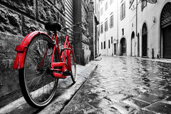 Retro vintage red bike on cobblestone street in the old town. Color in black and white. Old charming bicycle concept