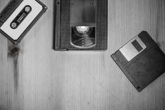 Retro vintage storage media from 90& x27;s : audio tape, video cassette vhs, floppy disk on wooden background in black and white. Wooden background stock photos