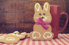 Retro vintage style Happy Easter bunny rabbit gingerbread cookies. With coffee mug on red check table with dark wood recycled timber background Stock Image