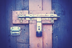 Retro vintage style picture of wooden door with lock. Stock Image
