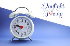 Retro vintage style white alarm clock on blue and white background with Daylight Saving sample text Stock Photo
