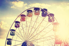 Retro vintage stylized picture of ferris wheel at sunset. Stock Photos