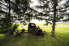 Retro vintage truck sitting between two trees. Old vintage retro vintage truck out back on farm land rotting away all rusty side view of door no bed sitting Royalty Free Stock Photos