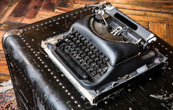 Retro Vintage Typewriter. Upper view of an old-fashioned typewriter on a leather chest with wooden floor Stock Images