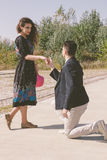 Retro vintage young man kneeling and asking a girl to marry him Stock Image