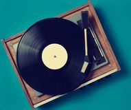 Retro vinyl player on a blue background. Entertainment 70s. Listen to music. Top view stock photography