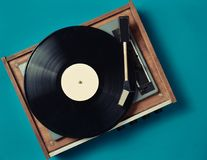 Retro vinyl player on a blue background. Entertainment 70s. Listen to music. Top view Royalty Free Stock Images