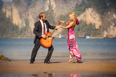 Retro-vista bionda e chitarrista di dancing sulla spiaggia Fotografie Stock