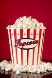 Retro- voller Kasten mit Popcorn und auf schwarzem reflektierendem Schreibtisch verschüttet stockfotos