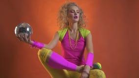 Retro vrouw danst terwijl het zitten met een discobal in haar hand stock videobeelden