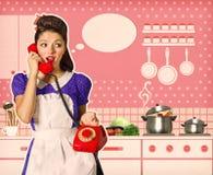 Retro vrouw die op telefoon in haar keukenbinnenland spreken royalty-vrije stock afbeeldingen