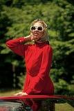 Retro vrouw in het rode uitstekende auto drijven op wegreis stock afbeeldingen