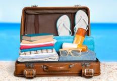 Retro walizka z podróżą protestuje na plaży Fotografia Stock