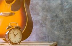 Retro- Warnungsschwarzuhr-Weinleseart und Akustikgitarre, die gegen auf Holztisch einen leeren Zementwandhintergrund stillsteht lizenzfreie stockfotos