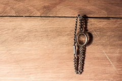 Retro watch without mechanism. Old watch with chain belt hanging on a nail on the wooden wall Stock Photo