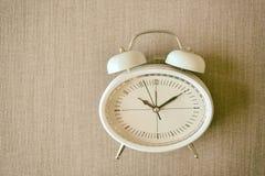 Retro- Wecker auf einem Bett Foto in der Retro- Farbbildart Stockfotografie